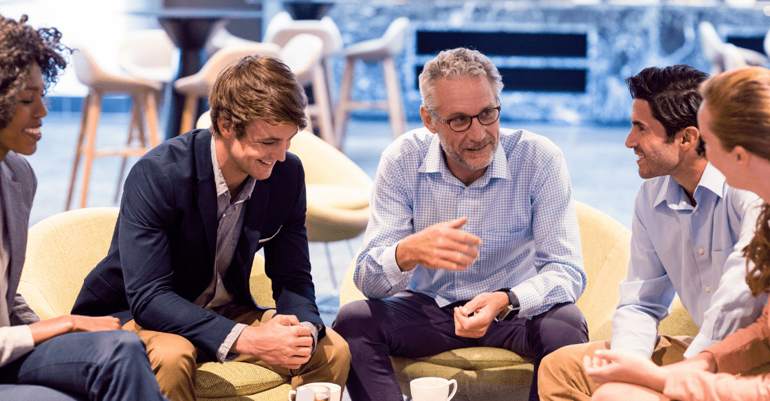 A team meets for coffee while their manager exhibits a laissez-faire type of leadership.