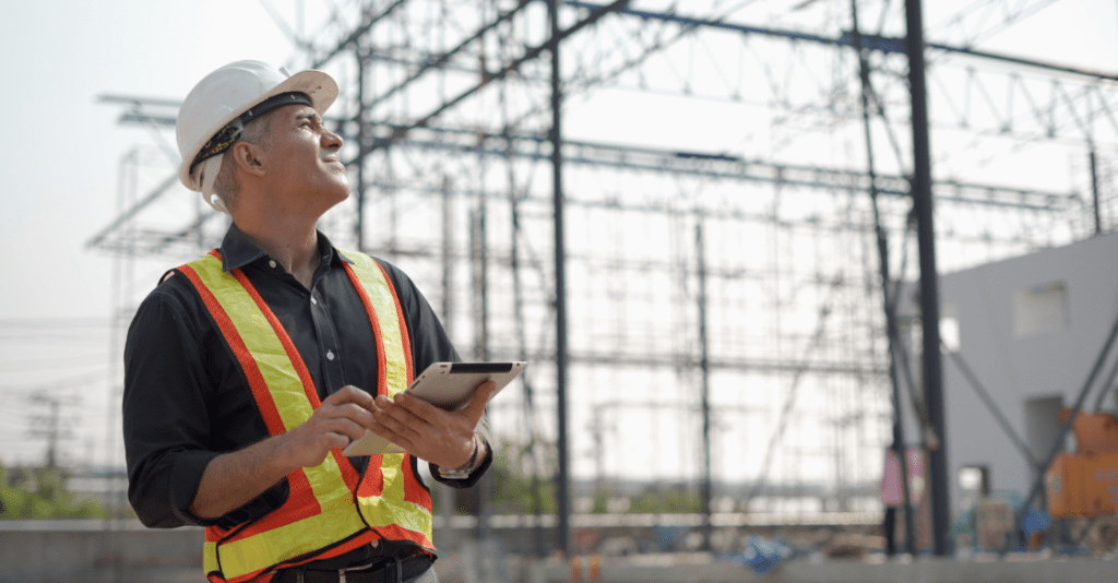 A construction worker squints in the heat while monitoring the weather on his tablet.